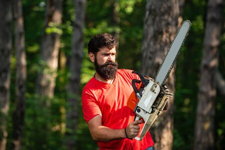 Firewood as a renewable energy source. Stylish young man posing like lumberjack. Firewood as a renewable energy source. Lumberjack with chainsaw on forest background. Stock Photo