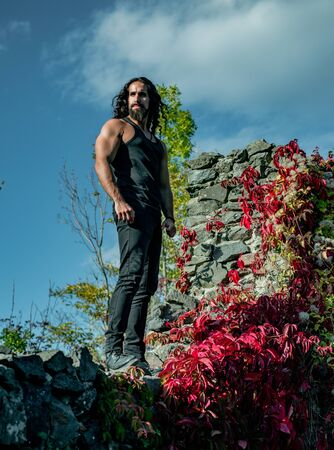 Young strong muscular man standing on edge of rock mountain with ivy leaves and looking straight. Portrait of fashion man model wearing dark clothes posing on blue sky background. Zdjęcie Seryjne