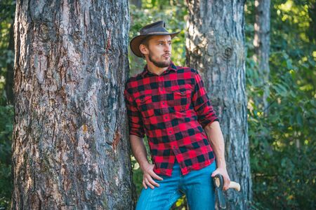 Handsome man lumberjack with a large ax examines the tree before felling. Agriculture and forestry theme. Logging.