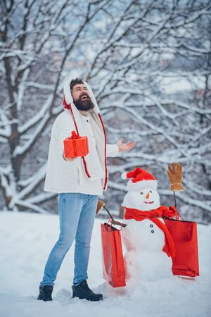 Snowman and funny bearded man with gift - the friends. Christmas banner. Snowman and funny bearded man in the snow. Christmas winter people portrait.