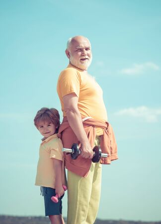 Grandfather and child do morning exercise. Grandfather and son doing exercises. Healthy life and sport concept.