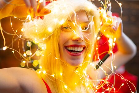 Pretty sexy blonde new year young woman in christmas santa red hat with fur in corset holding christmas lights. Christmas time. Gift card concept. Shopping sale. Present box. Stockfoto