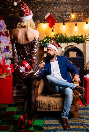 Drunk Girls celebrate New Year. Christmas home interior. Cute young woman and handsome man with Santa dress. Christmas time for happy young family.