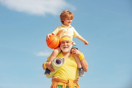 Grandfather and grandson with basketball ball and yoga mat in hands. Father and son having workout. Age is no excuse to slack on your health.