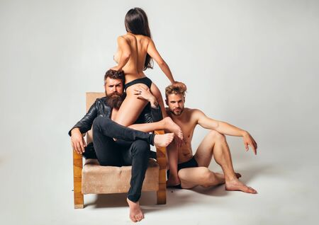 Sexy naked woman love in with two handsome bearded men. Group sex games at luxury chair. Full of desire men and woman menage going to have a sex. Three hot sex partners. Imagens