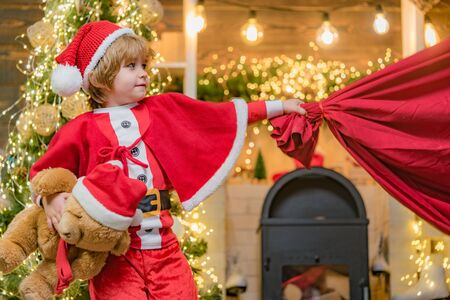 Surprised Little Santa in Christmas room. Adorable child play Santa at home. Santa Claus kid boy with a bag full of presents. Funny little Santa Claus with huge red bag with presents.