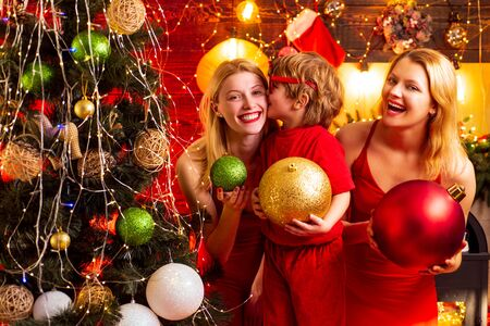Young beautiful Girls and small little kid by the Christmas tree.Ready to the party. Christmas decoration. Little kid is kissing his sister.