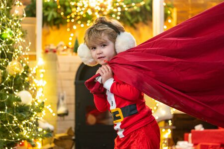 Santa child. Santa helper holding a red bag with presents. Merry christmas and happy new year. Surprised Little Santa in Christmas room. Stockfoto