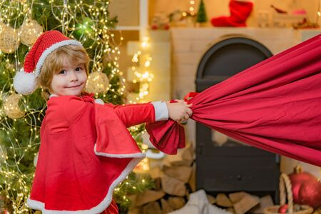 Adorable child play Santa at home. Santa helper with a huge bag. Family holiday. Little Santa huge bag run to delivery christmas gift. Stockfoto