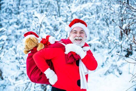 Sankt magischer Nebel, der entlang des Feldes geht. Frohe Weihnachten. Der Weihnachtsmann kommt mit Geschenken von außen. Der Weihnachtsmann geht im Winter mit einer Tüte Geschenke auf schneebedecktem Feld. Standard-Bild