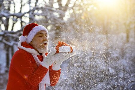 Merry Christmas and happy holidays. Portrait of happy Santa Claus walking in snowy forest and Blowing Magic Christmas snow. Stock fotó
