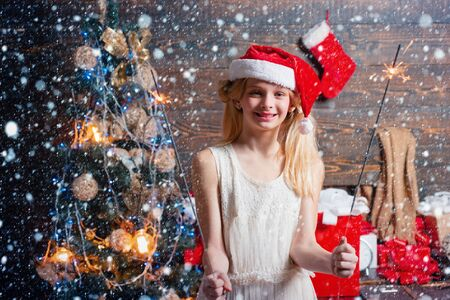 Happy Little girl with Christmas gift box. Cheerful cute Little girl opening a Christmas present. Opening gifts on Christmas and New Year. Funny kid holding Christmas gift. Stok Fotoğraf