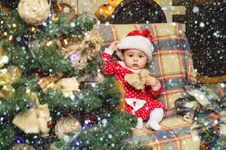 Child with a Christmas present on wooden background. Happy children. Christmas Babies. Cute little child is decorating Christmas tree indoors.
