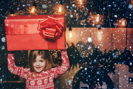 Christmas eve and magic concept. Bright New Years interior. The concept of giving and receiving gifts. Cheerful smiling happy little cute girl holding gigantic gift present from Santa.