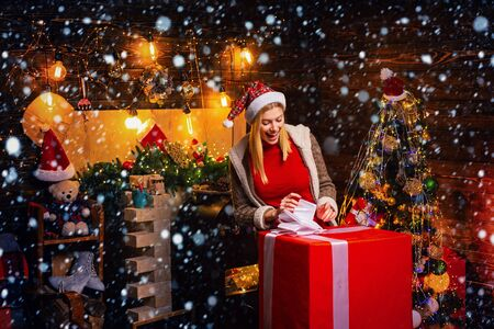 Merry Christmas and Happy Holidays. A happy and smiling face. Girl with christmas hat and many gifts celebrating the christmas holidays having big box. Archivio Fotografico - 135257010