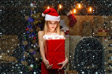 Portrait of happy Little girl looking at decorative toy ball by Christmas tree. Christmas teenager - happiness concept. Cute little girl teenager is decorating the Christmas tree indoors.