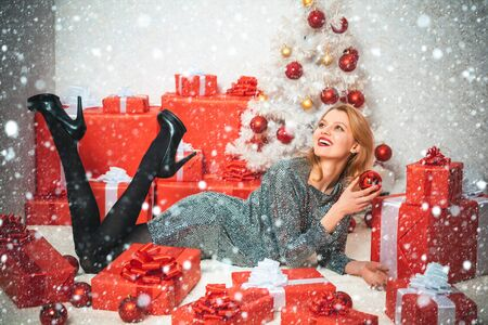 Cheerful young woman wearing Christmas costume over wooden wall. Event. Beautiful Woman with Christmas box gif at Home. New year gift. Happy emotion. Stock Photo