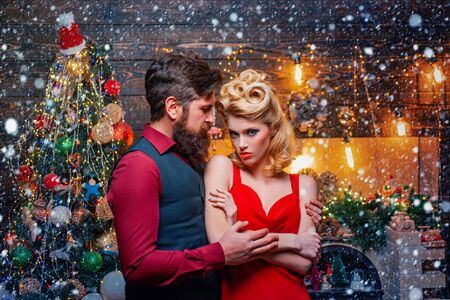 Young Christmas fashion couple. Happy couple with Christmas gift over Christmas interior background. New Year eve celebrating concept.