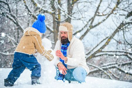 Happy family plaing with a snowman. Fathers day. Father and his son playing outdoors. Winter scene on white snow background.