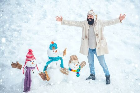 Merry Christmas and Happy Holidays. Christmas preparation - funny bearded man make snowman. Snowman and funny bearded man in the snow.
