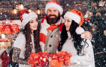 Cristmas friends in snow. Best friends. Happy people with christmas gift box. Merry Christmas and Happy Holidays. Joyful friends in christmas at home. Stock Photo
