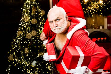 Christmas safety from burglars and home security. Funny bad Santa Claus with gift, bag with presents. Criminal christmas.