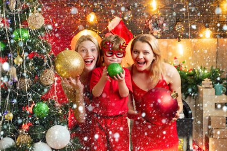 Christmas family in snow. Christmas family fun. Christmas party. Women red dresses celebrate christmas with little cute baby. Family bonds. Love peace joy. Kid boy with mom or aunts sisters having fun. Join celebration