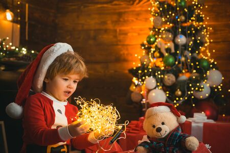 Little kid is playing with Christmas light on Christmas tree background. Kid is showing Chritmas light to his toy. Close up. Happy holidays, family.