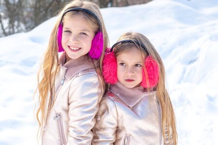 Dos niña jugando con nieve en el parque. Retrato de niños de invierno. Dos adorables niñas divirtiéndose juntas en el hermoso parque de invierno. Lindas hermanas jugando en la nieve.