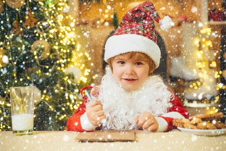 Christmas kids in snow. Portrait of Santa Claus writes the letter to children. Kid Santa Claus enjoying in served gingerbread cake and milk.