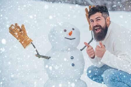 Christmas man in snow. Enjoying nature wintertime. Handsome bearded man, father in winter clothes. Christmas Man and snowman on white snow background.