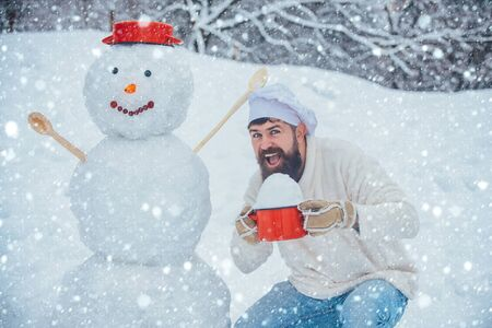 Happy father chef playing with a snowman on a snowy day Standard-Bild