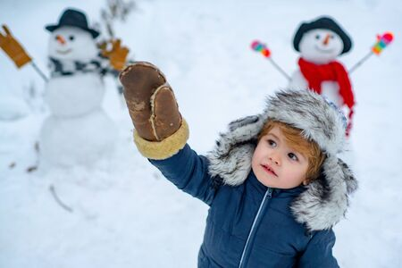 Child boy Having Fun in Winter Park. Winter clothes for kids. Happy winter time. Beauty child with snowman in frosty winter Park.