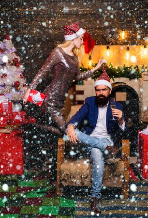 Christmas couple in snow. Handsome bearded hipster Santa with smiling positive young woman. Christmas tree at home. After Christmas shopping.