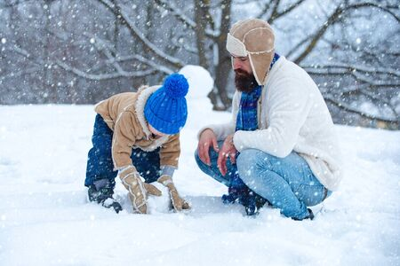 Christmas family in snow. Father and son making snowman. Christmas holidays and winter new year with father and son. Winter family in frosty winter Park. Thanksgiving day and Christmas.