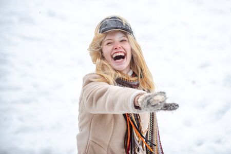 Young excited girl playing snowball fight. Happy woman holds snowball in hands. Portrait of a happy woman in the winter. Cheerful girl outdoors.