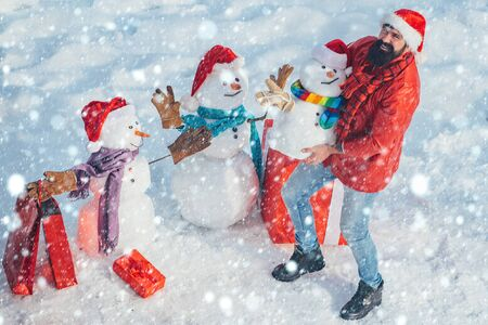 Christmas man in snow. Enjoying nature wintertime. Winter man. Christmas Man and snowman on white snow background. Snowman and funny bearded man the friend is standing in winter hat and scarf with red nose.