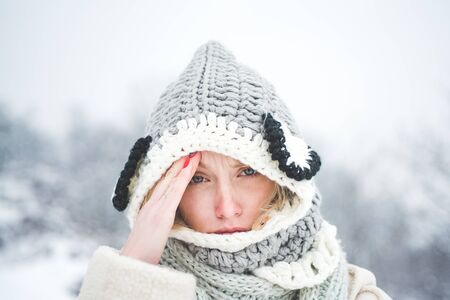 Allergy winter season. Portrait of beautiful young blonde touching her temples feeling stress, on snowy winter background. Stock Photo