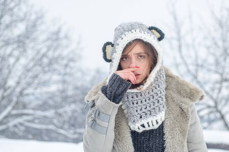 Sick in winter. Cold flu winter season, runny nose. Showing sick woman sneezing at winter park. Young woman blowing nose at snow winter background.