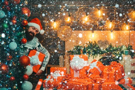 Man in snow. Bearded modern santa claus in knitted sweater. New year gift. Santa Claus gifting gift. Portrait of a brutal mature Santa Claus.