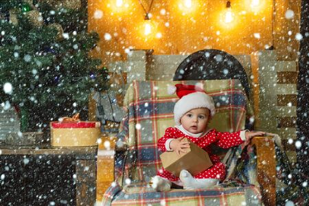 Kid in snow. Child with a Christmas present on wooden background. Christmas children. Cute little child is decorating Christmas tree indoors. Happy children. Stok Fotoğraf