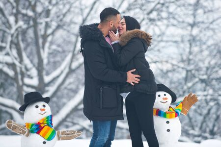 Winter adventure. Passionate man gently kissing beautiful woman with desire. Kissing winter couple portrait. 版權商用圖片