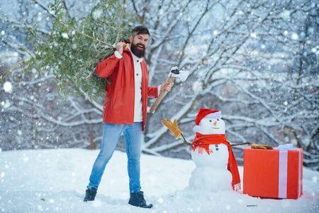 Mann im Schnee. Mann wird einen Weihnachtsbaum fällen. Wintergefühle. Bärtiger Mann mit frisch gefälltem Weihnachtsbaum im Wald. Frohe Winterzeit. Frohe Weihnachten und schöne Feiertage. Standard-Bild