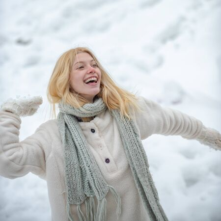 Happy winter time. Happy young girl playing snowball fight. Portrait of a happy woman in the winter. Cute playful young woman outdoor enjoying first snow. Stock Photo