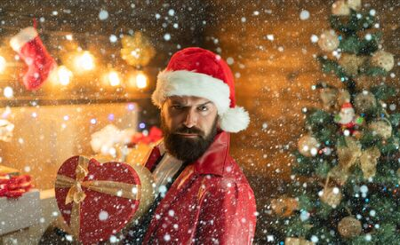 Man in snow. Santa claus with Christmas gifts. New year gift box. Bearded modern santa wishes Merry christmas and Happy new year. Imagens