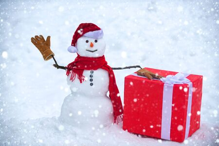 Snowman the friend is standing in winter hat and scarf with red nose. Christmas snowman on white snow background. Snow man with gift Stock Photo