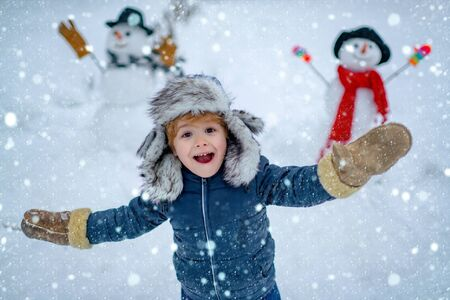 Enjoying nature wintertime. Child in snow. Winter kid. Funny boy posing on winter weather. Snowman and funny little boy kid in the snow. Snowman