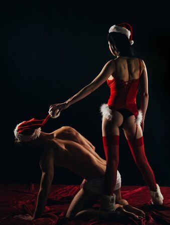 Christmas sexy party. Slavery concept. Dominant girl in Santa hat. BDSM games with domination and submission.