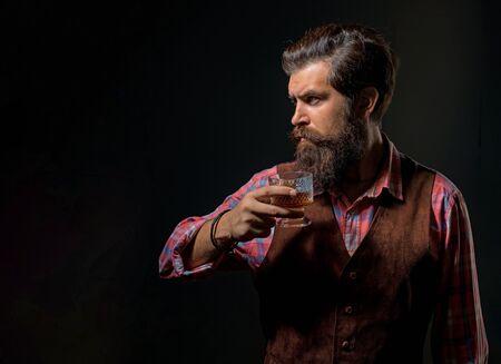 Mann mit Bart hält ein Glas Brandy. Luxuriöses alkoholisches Getränk. Fröhlicher bärtiger Mann trinkt teuren Whisky.
