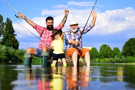 Male multi generation family. Grandfather, father and grandson fishing together. Father teaching his son fishing against view of river and landscape. Stock Photo - 136806254